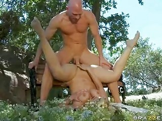 Muscled bald stud drilling busty blonde on bench in park