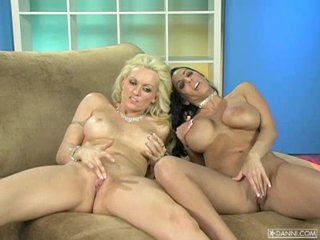 Busty 10-Pounder tease Monica Mayhem plays with a girlfriend on the sofa